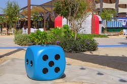 Oversize blue dice shaped chair with five dots at the playground. Blue huge gambling cube as a creative decision for urban furniture.