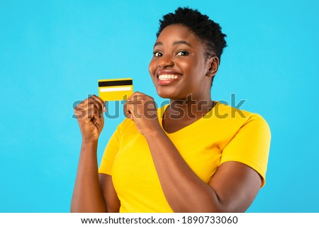 Oversized African Woman Holding Yellow Credit Card Showing It To Camera Advertising Bank Posing Over Blue Studio Background. Banking, Money And Finance, Financial Advertisement Concept