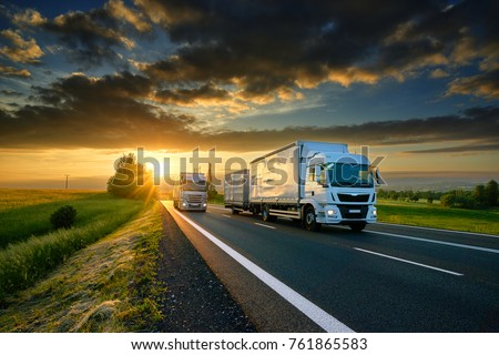 Overtaking trucks on an asphalt road in a rural landscape at sunset #761865583