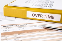 Overtime words on document binder place on blank weekly time sheets