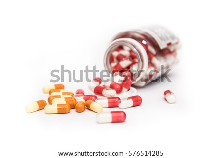 Overturned bottle with colored pills isolated on white background. #576514285