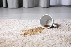 Overturned cup and spilled tea on beige carpet, closeup. Space for text