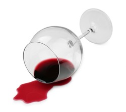 Overturned glass and spilled wine on white background