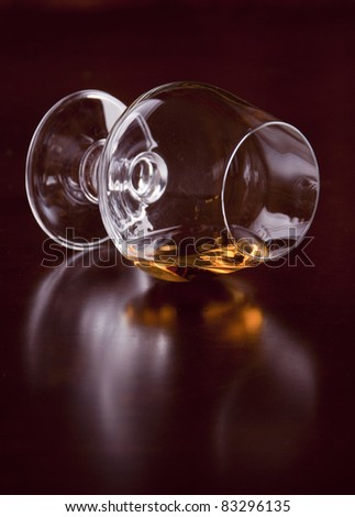 overturned glass of brandy over brown background