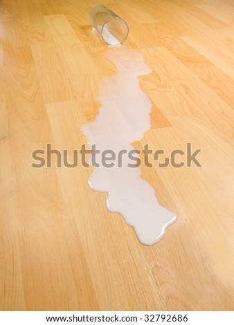 Overturned glass of milk illustrating proverb, do not cry over spilt milk - stock photo