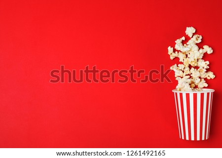 Overturned paper cup with tasty popcorn on color background, top view. Space for text #1261492165