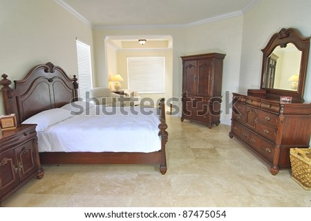 Overview of a beautiful classic bedroom suite in a private residence with a travertine floor