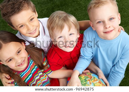 Overview of four children looking up and smiling cheerfully - stock photo
