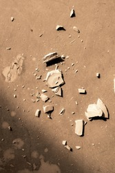 Overview of smithereens of broken clay item on flat brown surface that can be used as background
