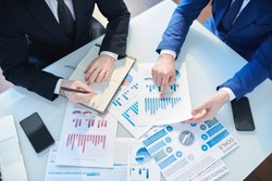Overview of two businessmen discussing financial papers by desk while organizing work and analyzing statistics