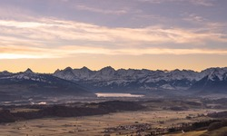 overview swiss landscape with hills forests mountains in warm color during sunset or sunrise and epic sky