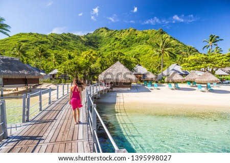 Overwater bungalow hotel resort in Tahiti, Moorea island. Person on holiday relaxing at French polynesia luxury destination. #1395998027