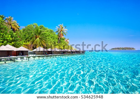 Stock Photo Overwater bungalows on tropical island with sandy beach, palm trees and turquoise clear water