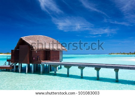 Overwater villas in blue lagoon of a tropical island