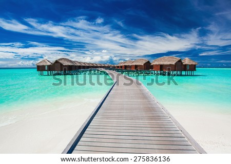 Overwater villas on the tropical lagoon connected to island by jetty stock photo