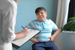 Overweight boy consulting with doctor in office