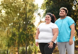 Overweight couple in sportswear together in park