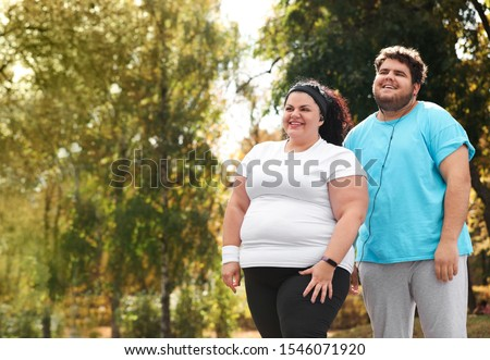Overweight couple in sportswear together in park ストックフォト ©