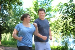 Overweight couple running in green park
