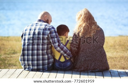 Overweight couple with son near river on sunny day