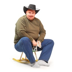 Overweight cowboy riding on a rocking horse.