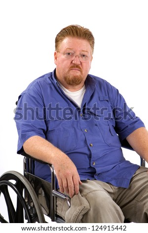 Overweight disabled man sits in a wheelchair with a sad expression on his face.