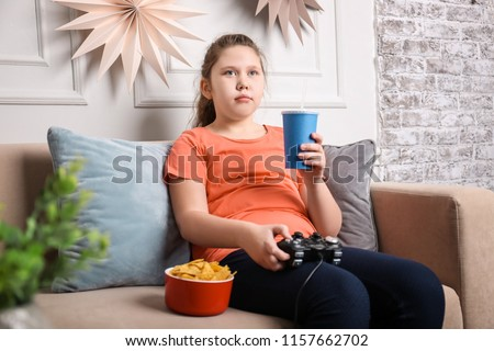 Overweight girl playing videogame with snacks indoors