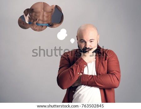 Overweight man dreaming about muscular body on grey background. Weight loss concept
