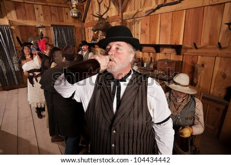 Overweight man drinks from a bottle of alcohol in a saloon