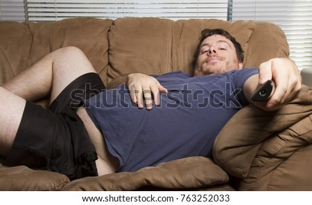 overweight man just watching tv on the couch