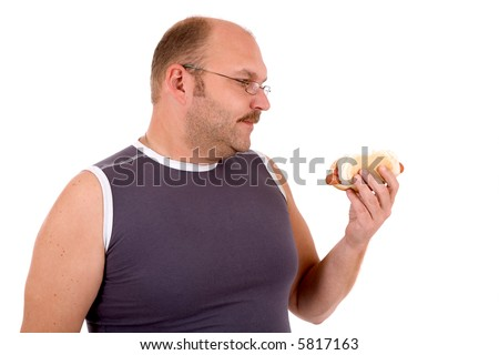 Overweight man looking at the hot dog in his hand