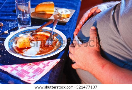 Shutterstock Overweight man resting after eating too much food.