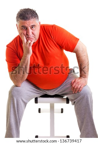 Overweight man sitting on a bench for abdominals, he takes a break, isolated on white background - stock photo