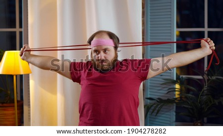 Overweight man stretching home using sports equipment. Portrait of fat guy with skipping rope exercising in living room losing weight. Stout male working out at home Foto stock ©