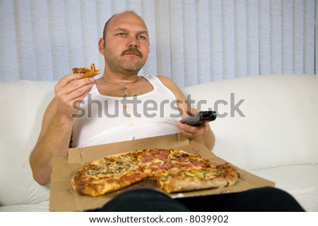 Overweight mature man sitting on the couch with a pizza and the remote control