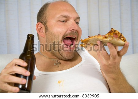 Overweight mature man with pizza in one hand and a beer in the other