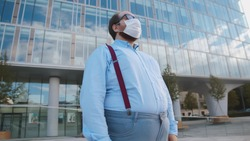 Overweight office employee tired of wearing safety mask outdoors. Portrait of obese businessman standing near office building in facial mask