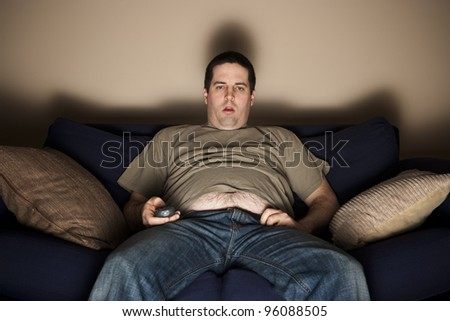 Overweight slob watches TV with belly showing Сток-фото ©