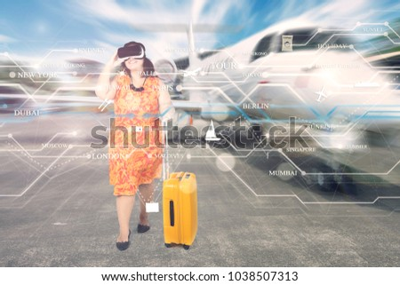 Overweight traveler using virtual reality glasses in the airport to choose the city of her destinations  #1038507313
