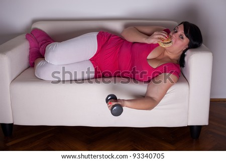 Overweight woman eating a burger, watching tv and lifting weights. Selective focus.
