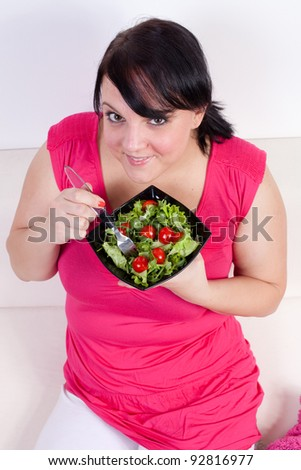 Overweight woman eating a salad. Selective focus.