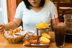 Overweight woman eating junk food.