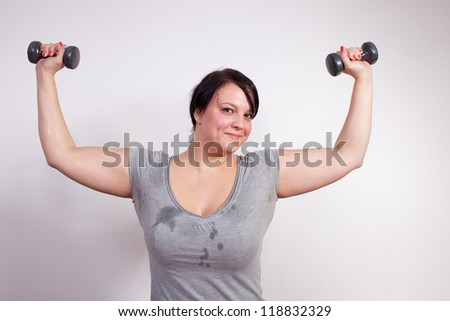 Overweight woman exercising, lifting weights