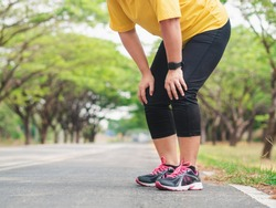 Overweight woman feeling tired while running in the park. Weight loss concept