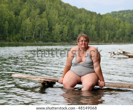 overweight woman sitting on stage in lake