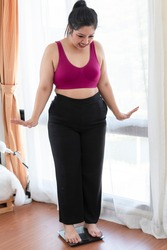 Overweight woman standing on weight scale in bedroom. Obese woman with measure tape and weighing machine. Overweight woman standing on weighing machine. Surprise female on weighing machine at home.