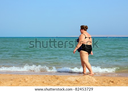 overweight woman walking on sea beach