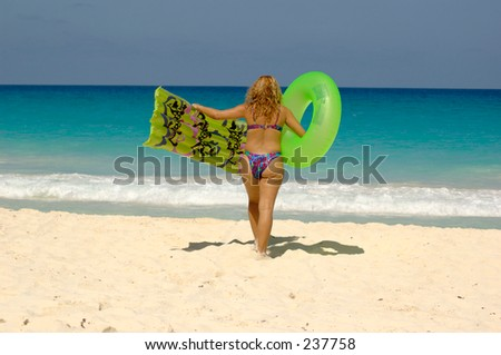 Overweight woman walking towards the sea. Celulite.