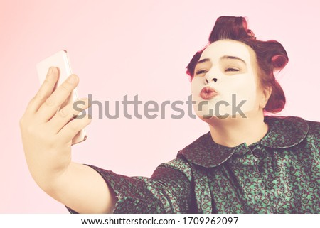 overweight woman wearing pink bathrobe and with beauty mask and curlers making a selfie with her smartphone on pink studio isolated background