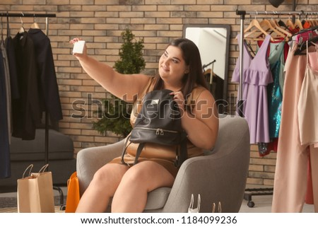 Overweight woman with new backpack taking selfie in shop